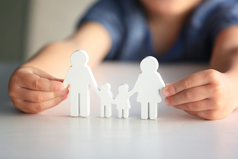 Child holding figure in shape of happy family, closeup. Adoption